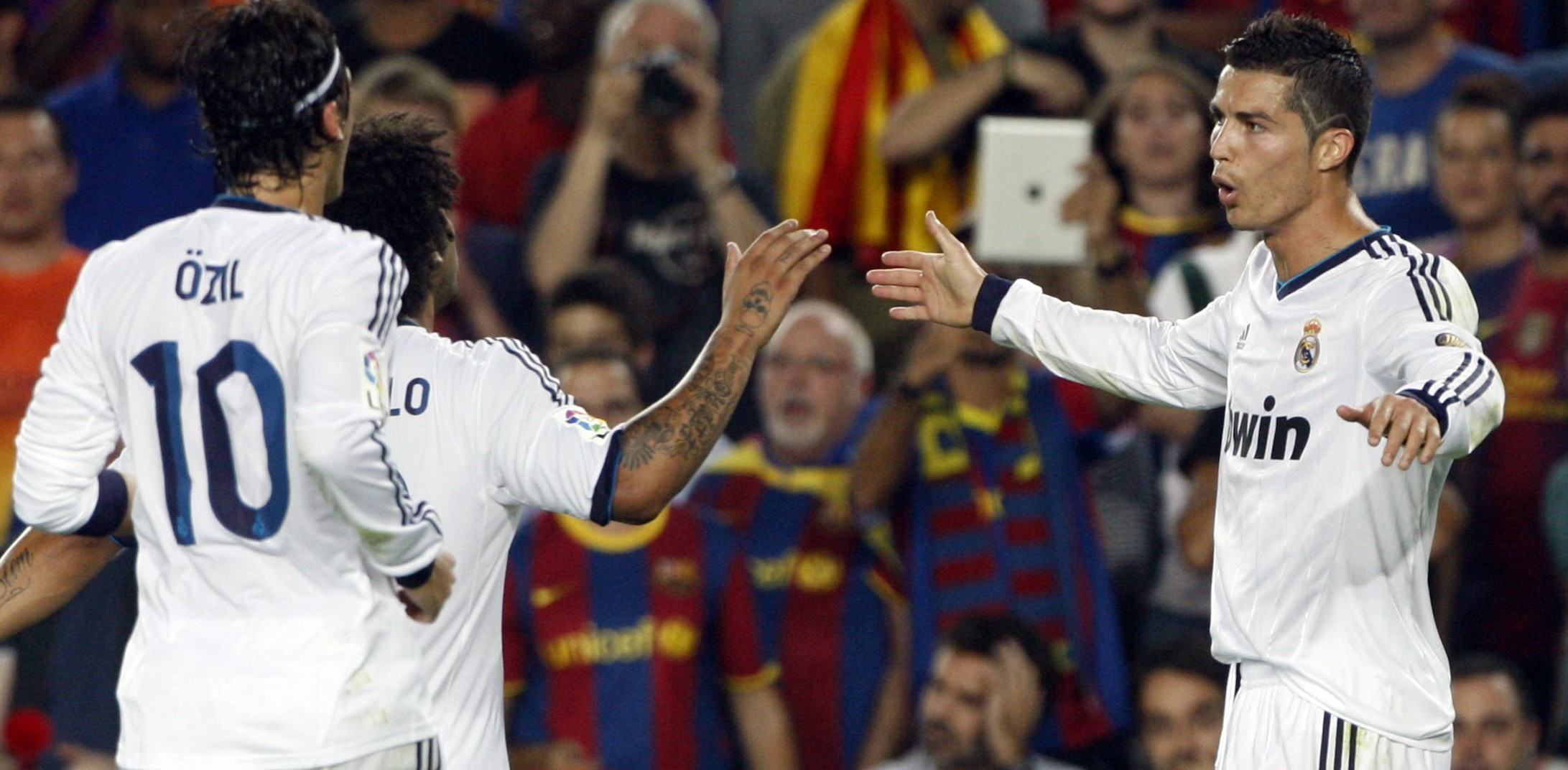 Real Madrid's Ronaldo celebrates with Ozil and Marcelo after scoring his second goal against Barcelona during their Spanish first division soccer match at Nou Camp stadium in Barcelona